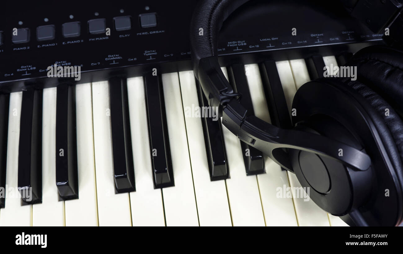 Black headphones over an electric piano - Stock Image