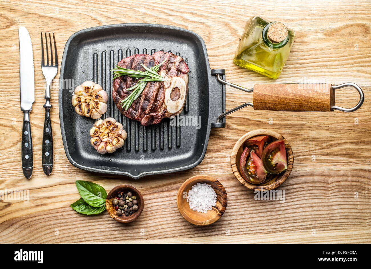 Beef steak with spices on pan on wooden table. - Stock Image