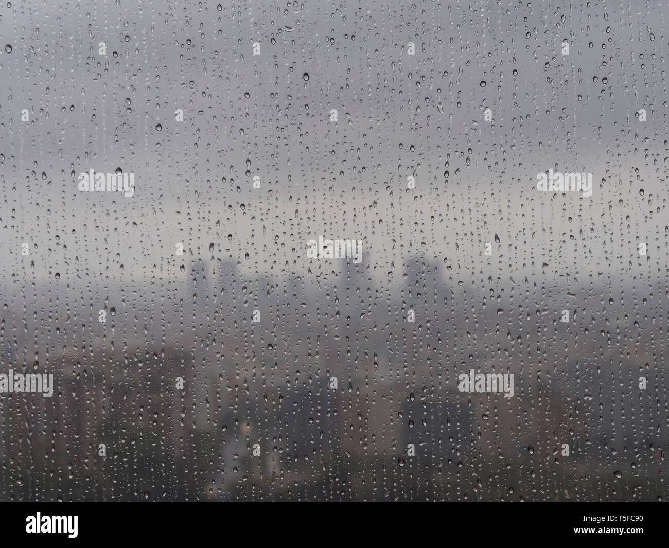 After heavy rainfall, the diffuse skyline of Barcelona is emerging in the twilight behind raindrops on a window. Stock Photo