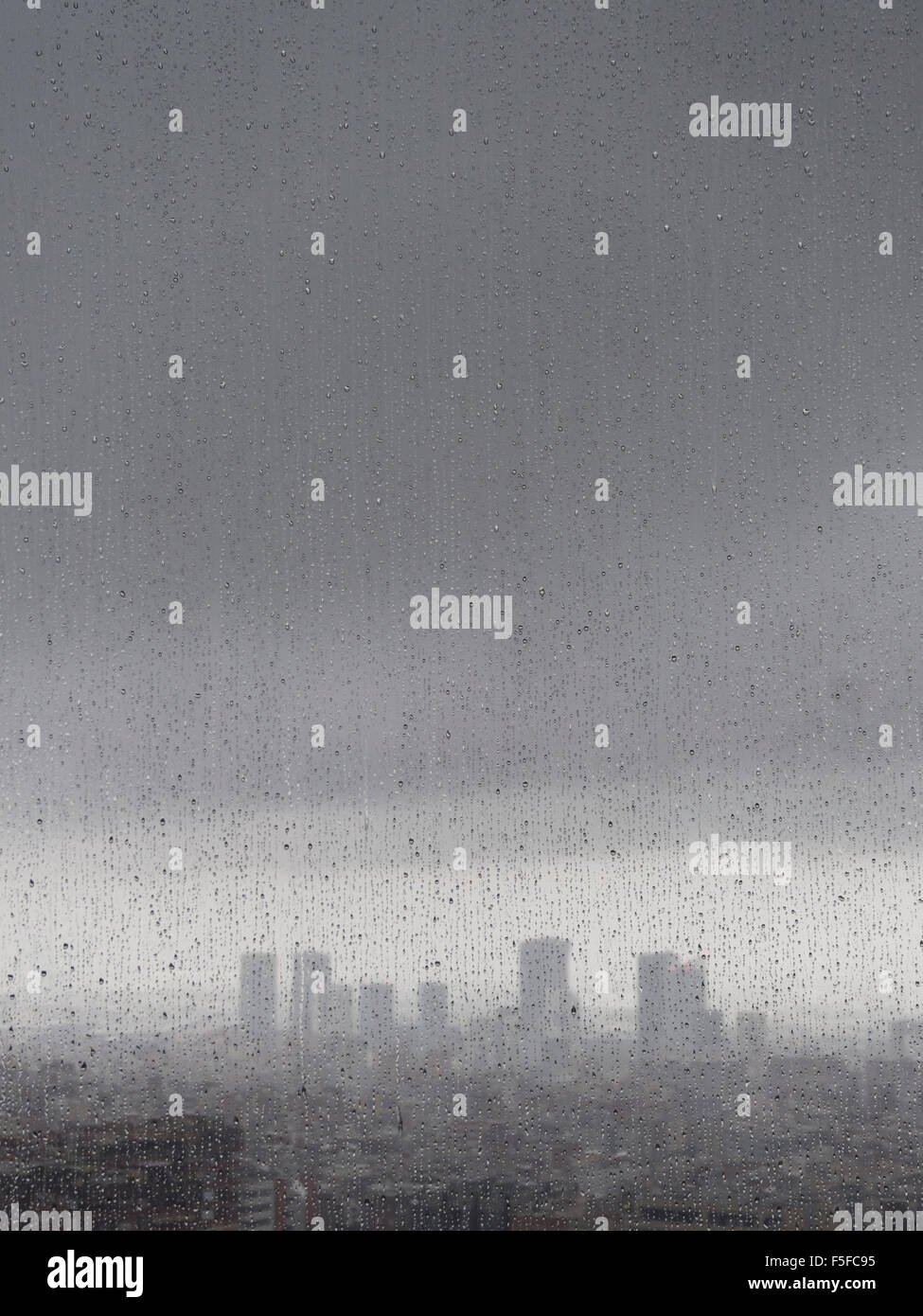 After heavy rainfall, the diffuse skyline of Barcelona is emerging in the twilight behind raindrops on a window. - Stock Image