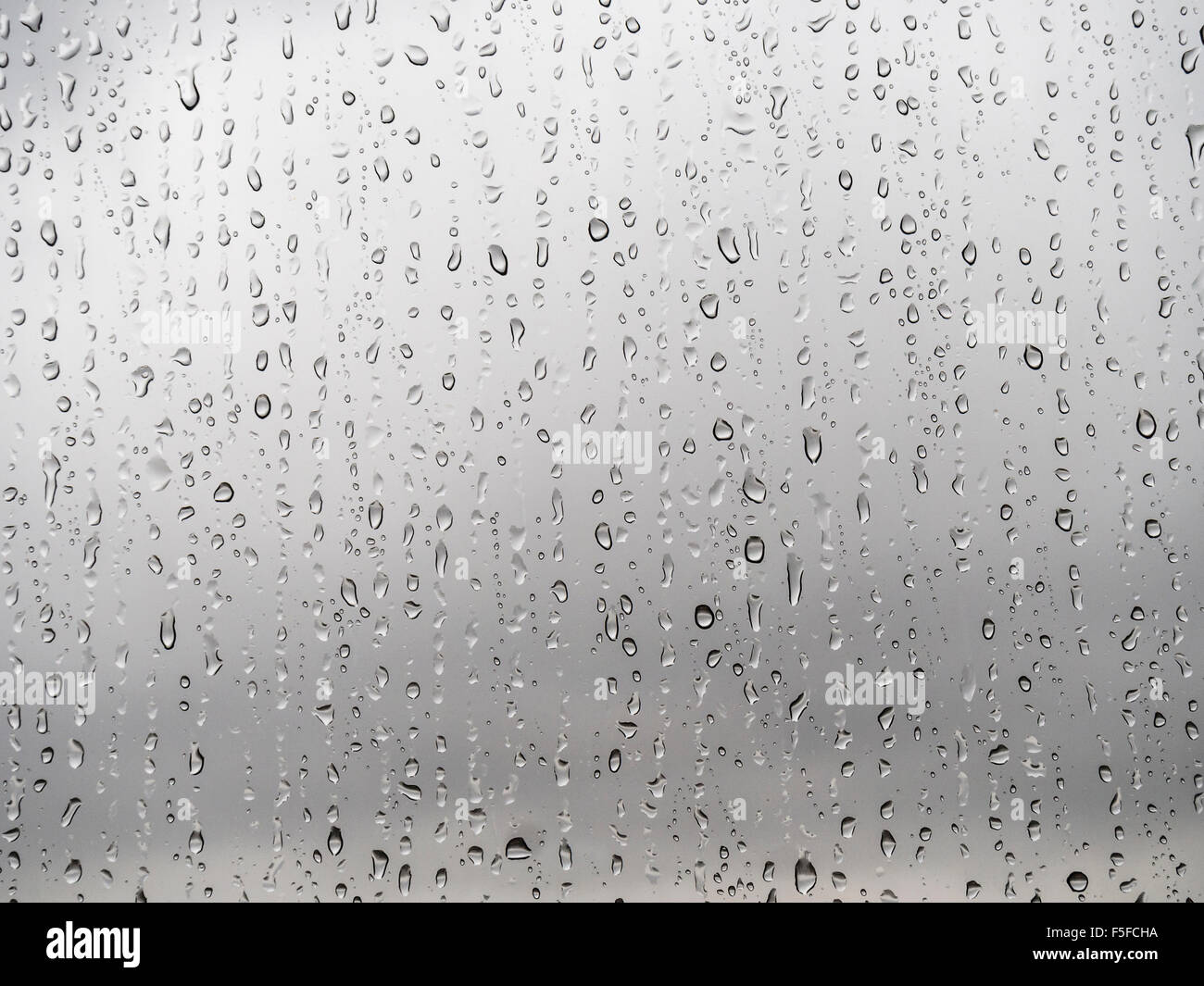 After heavy rainfall, many raindrops are trickling down a translucent glass window. Blurred, sad, grey sky in the - Stock Image