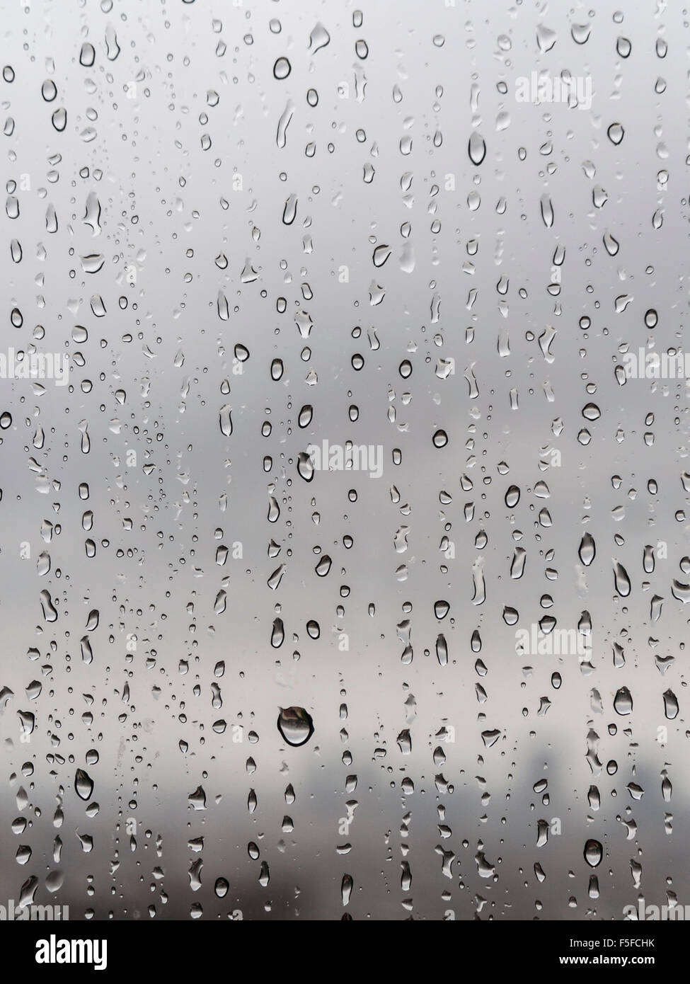 After heavy rainfall, many raindrops are trickling down a window. Diffuse silhouette of a city skyline emerges in Stock Photo