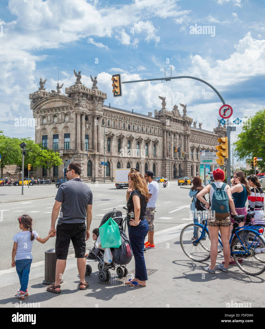 Spain, Catatonia, Barcelona, Port Vell, tourists at Portal des Pau with view of the Aduana building - Stock Image