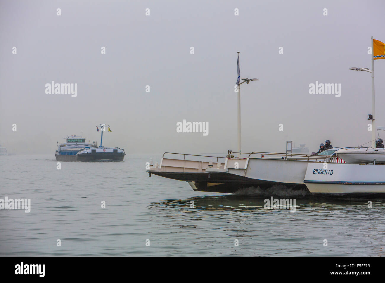 River Rhine, near Bingen, Germany, fog, low visibility, car ferry boat, freight ship, - Stock Image