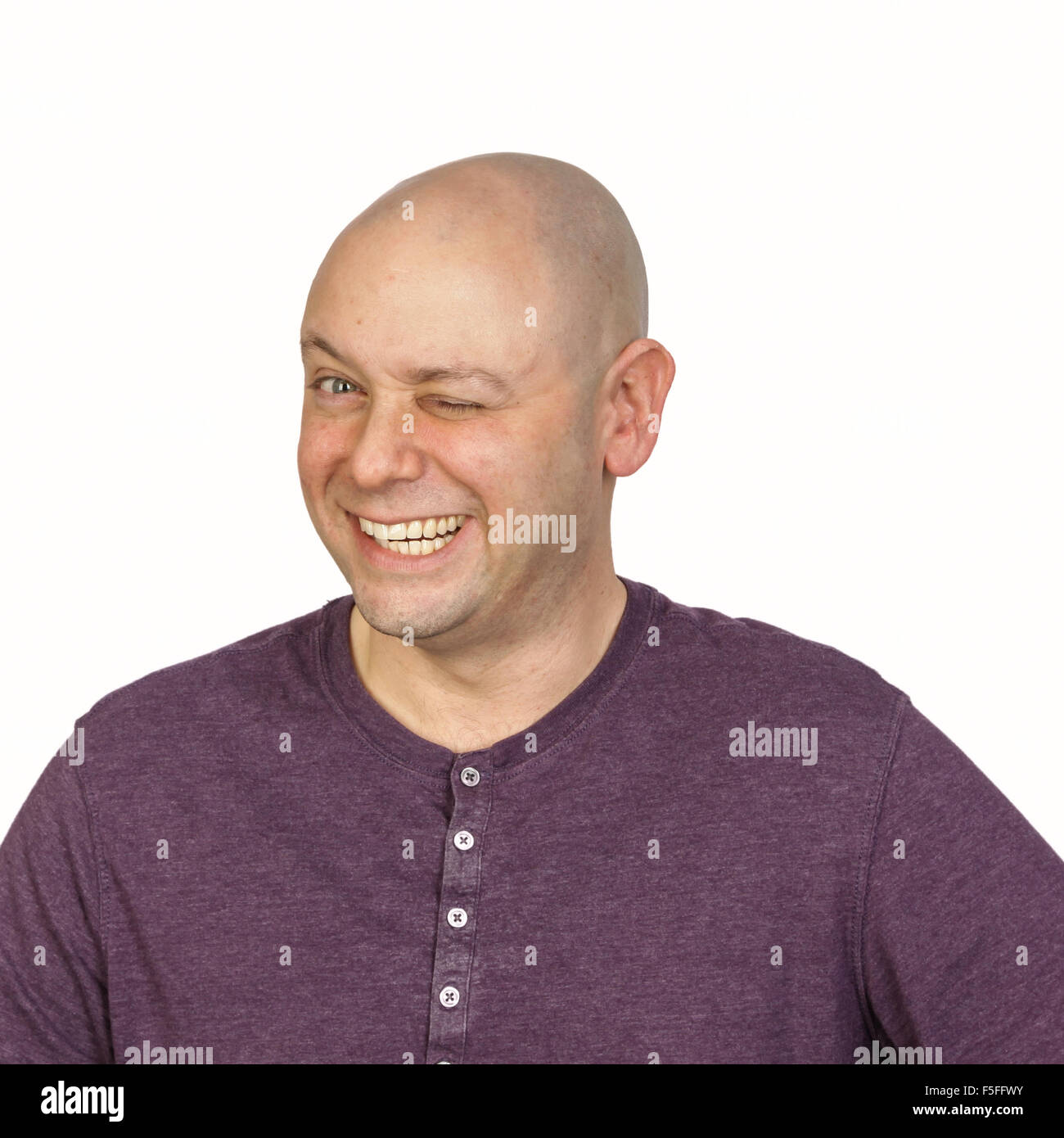 Big wink by a bald man in studio on white background. He is wearing a purple buttoned t-shirt with a round neck. - Stock Image