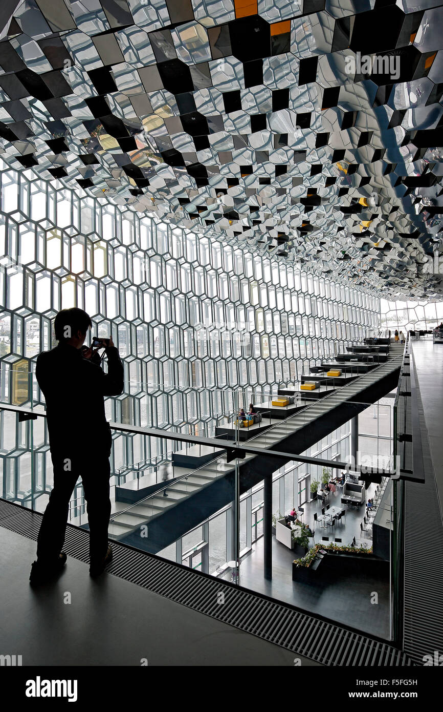Woman photographing interior of Harpa Concert Hall and Conference Center, Reykjavik, Iceland - Stock Image