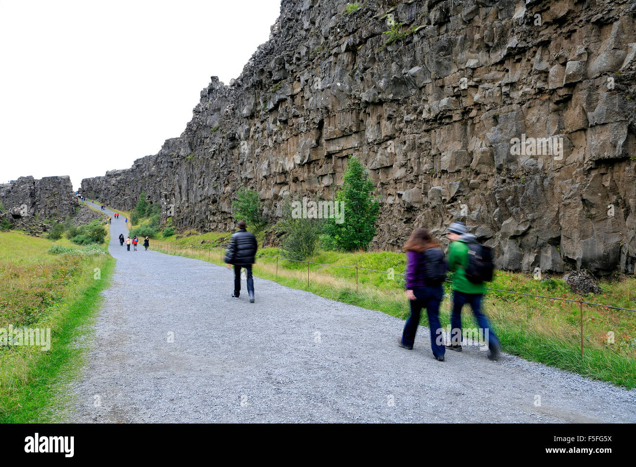 People on trail by volcanic rock walls (Eurasian and North-American  tectonic plates collide), Thingvellir National Park, Iceland 7ad9a7bb8ce8