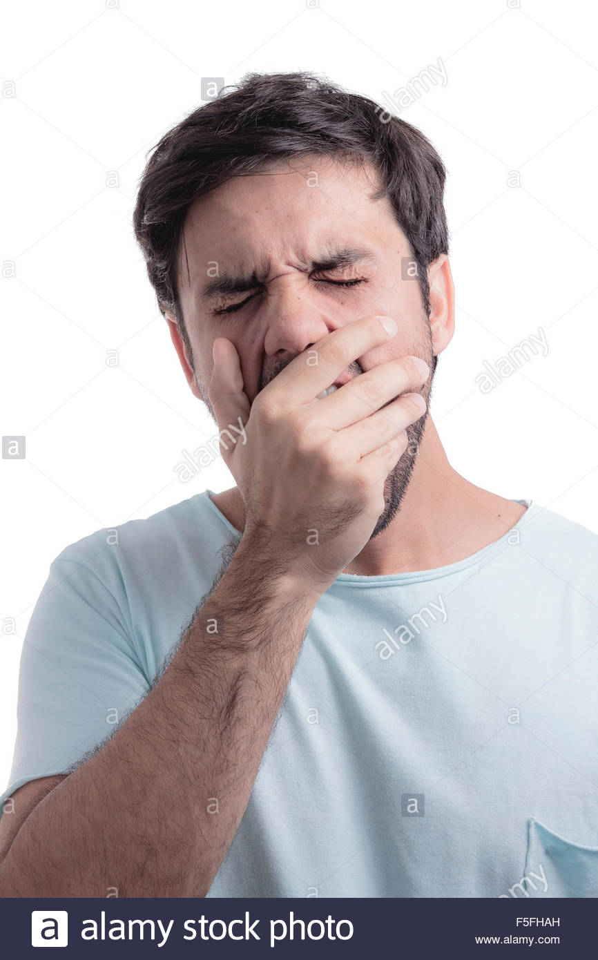 Young man yawning with his hand on face - Stock Image
