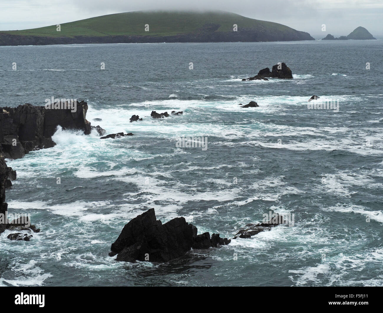 Turbulent sea with waves crashing into cliffs near Dunquin on Dingle peninsula Ireland with cloudy Blasket Islands Stock Photo