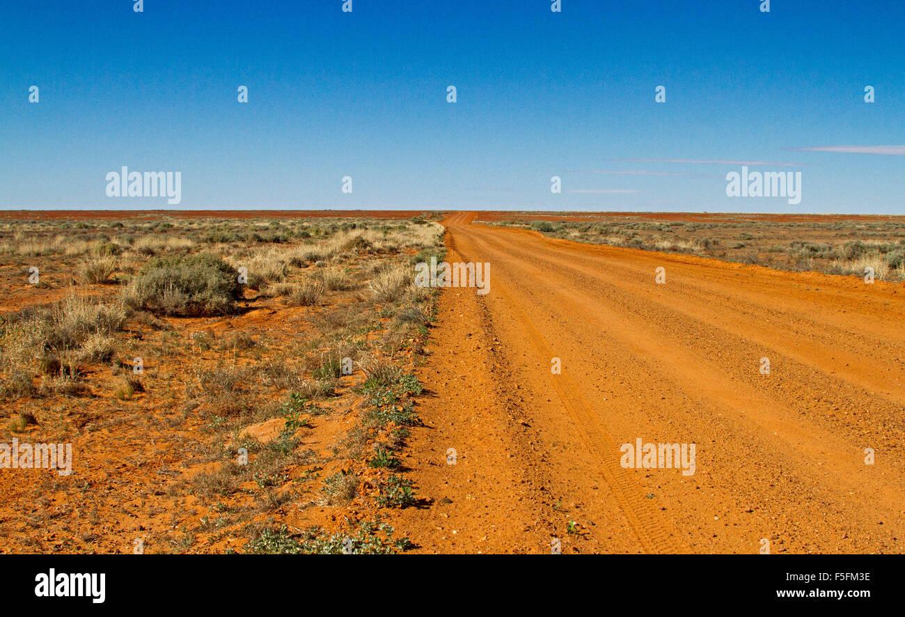 Long red dirt road in Australian outback stretching across arid treeless plains of  Flinders Ranges desert region - Stock Image