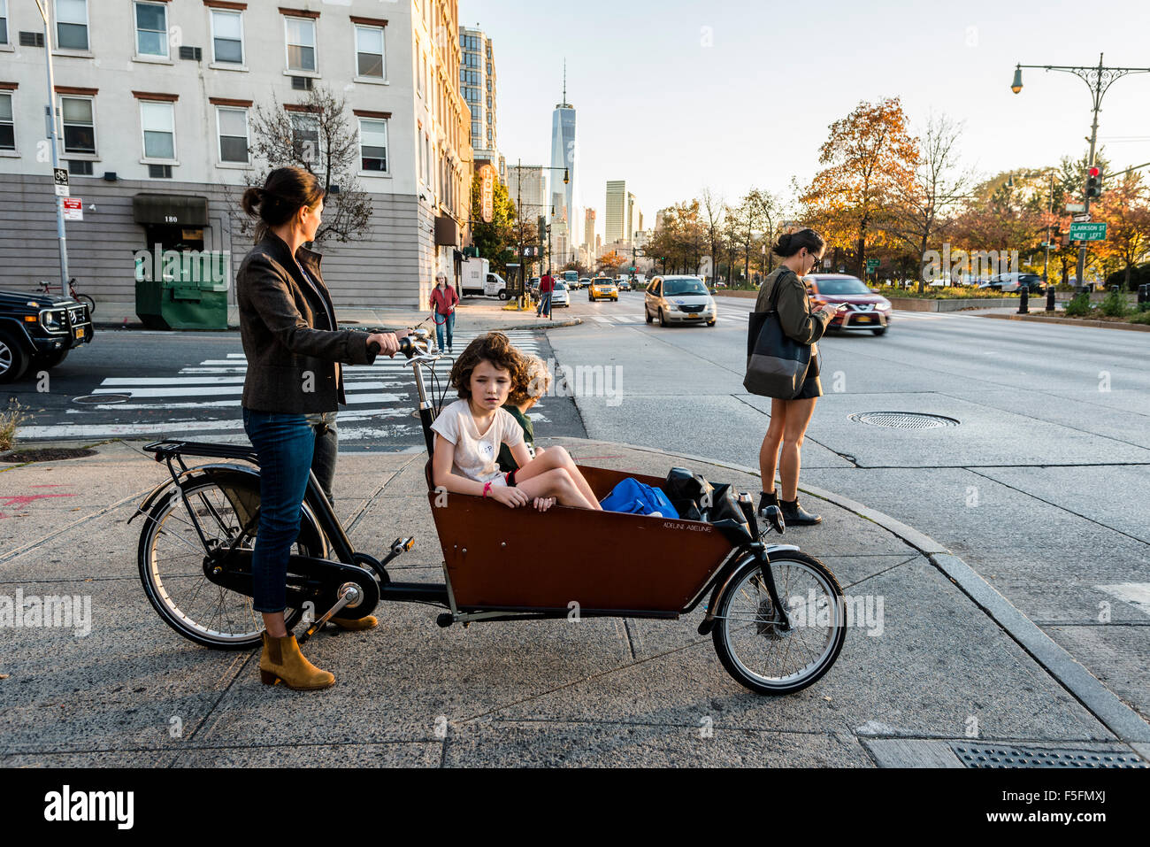 New York, NY - Mother and children in a bakfiet, or Dutch Utility Bike, wait on the sidewalk to cross the West Side - Stock Image