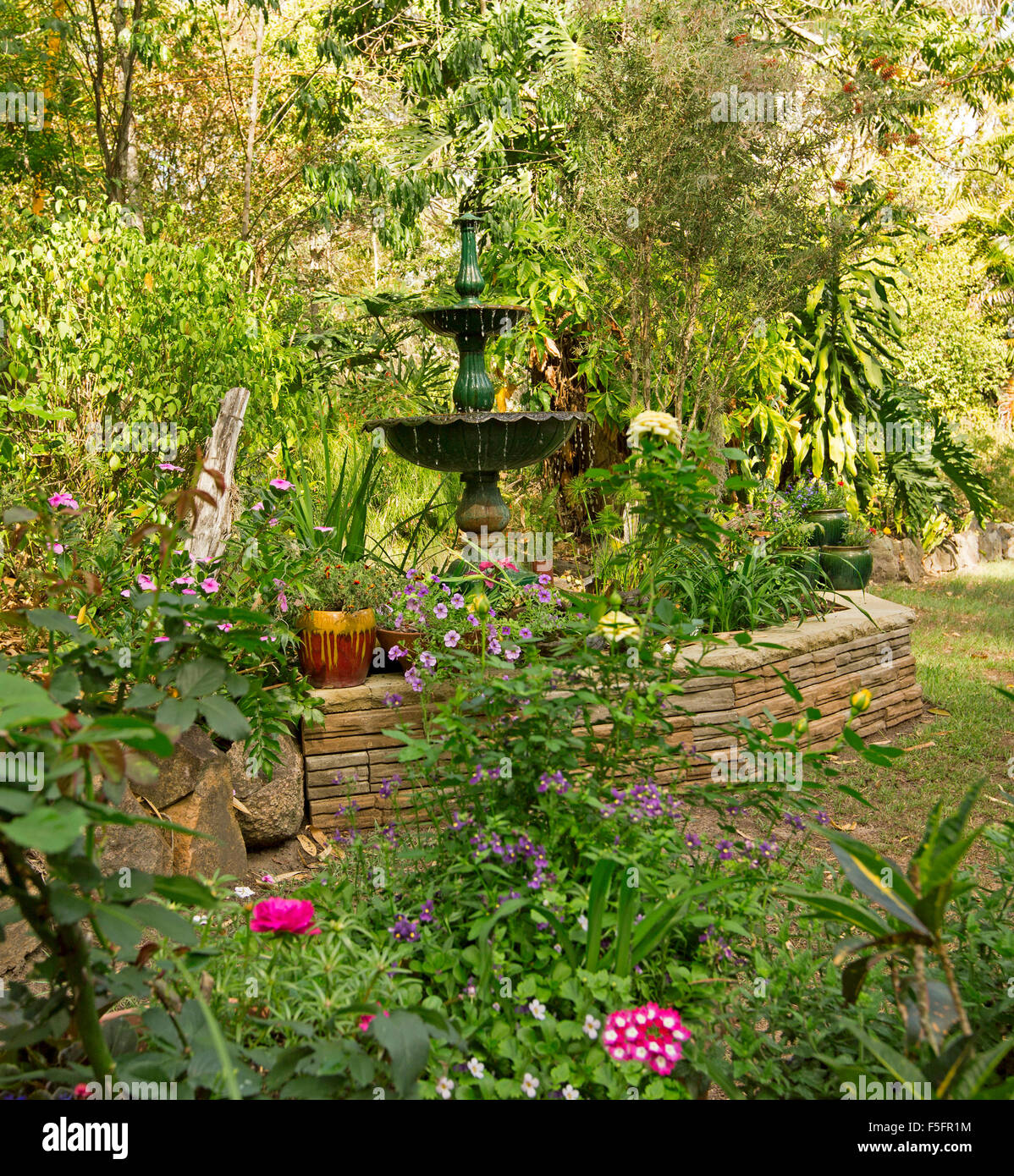 Decorative Garden Feature With Low Stone Wall, Ornate Fountain, Plants In  Containers, Hemmed By Lawn, Flowers, Shrubs, Trees