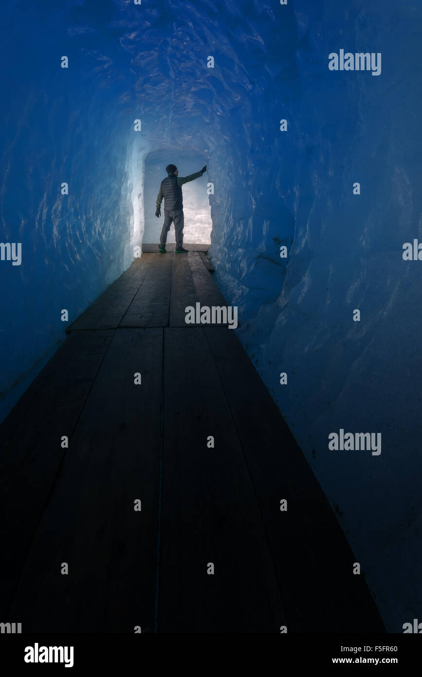 Man silhouette in ice cave. Rhone glacier, Switzerland, Europe. - Stock Image