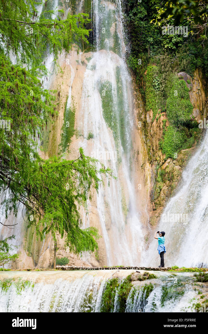 A woman photographs the Minas Viejas Waterfalls, one of the most colorful in all of Mexico. - Stock Image