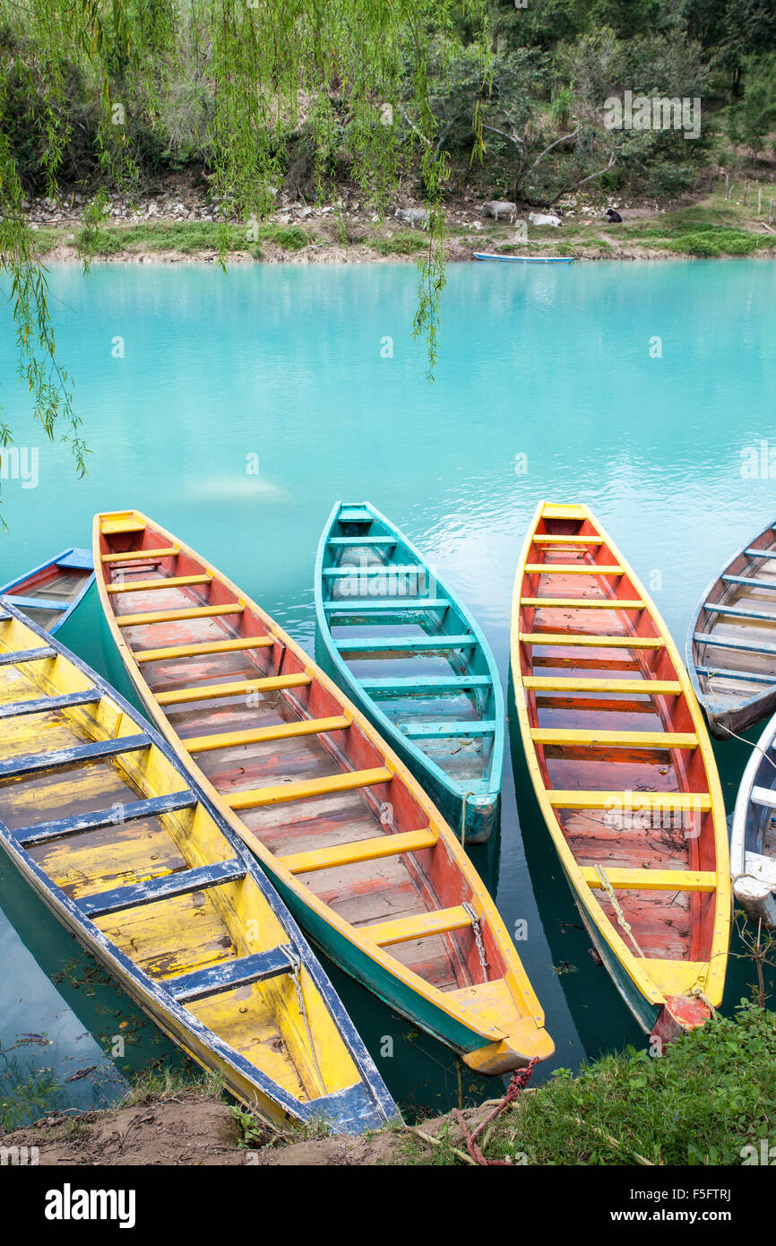 Colorful canoes line the shore of the Tampaon River in the Huasteca Potosina area of San Luis Potosi, Mexico. - Stock Image