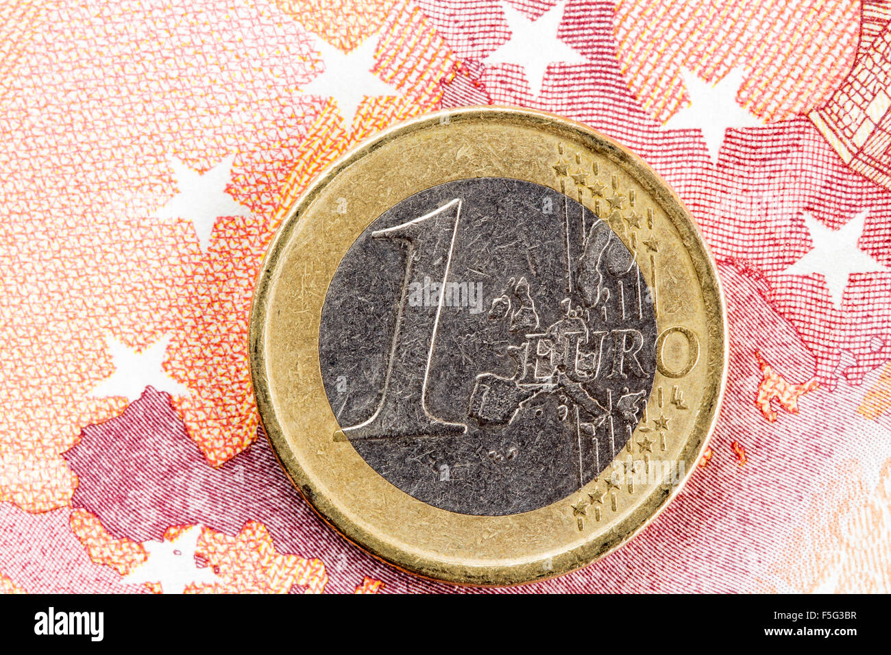 Detail of one euro coin on red ten euro banknote background - Stock Image