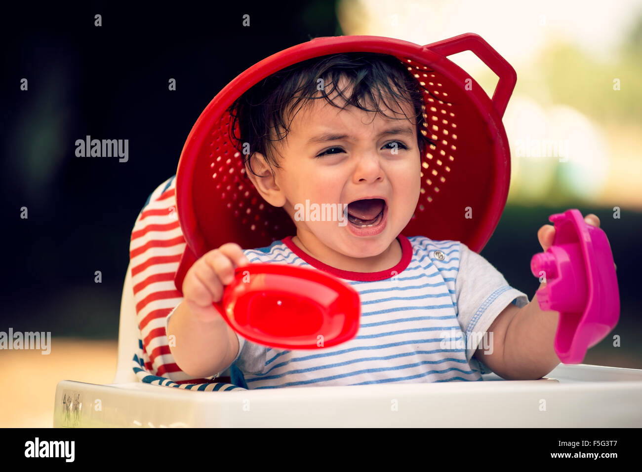 child eight month old on high chair plays outdoors in springtime - Stock Image