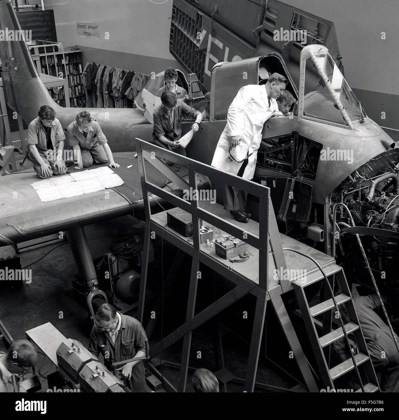 historical, 1950s, aircraft engineering or technical students working on an aircraft's engine under supervision, - Stock Image