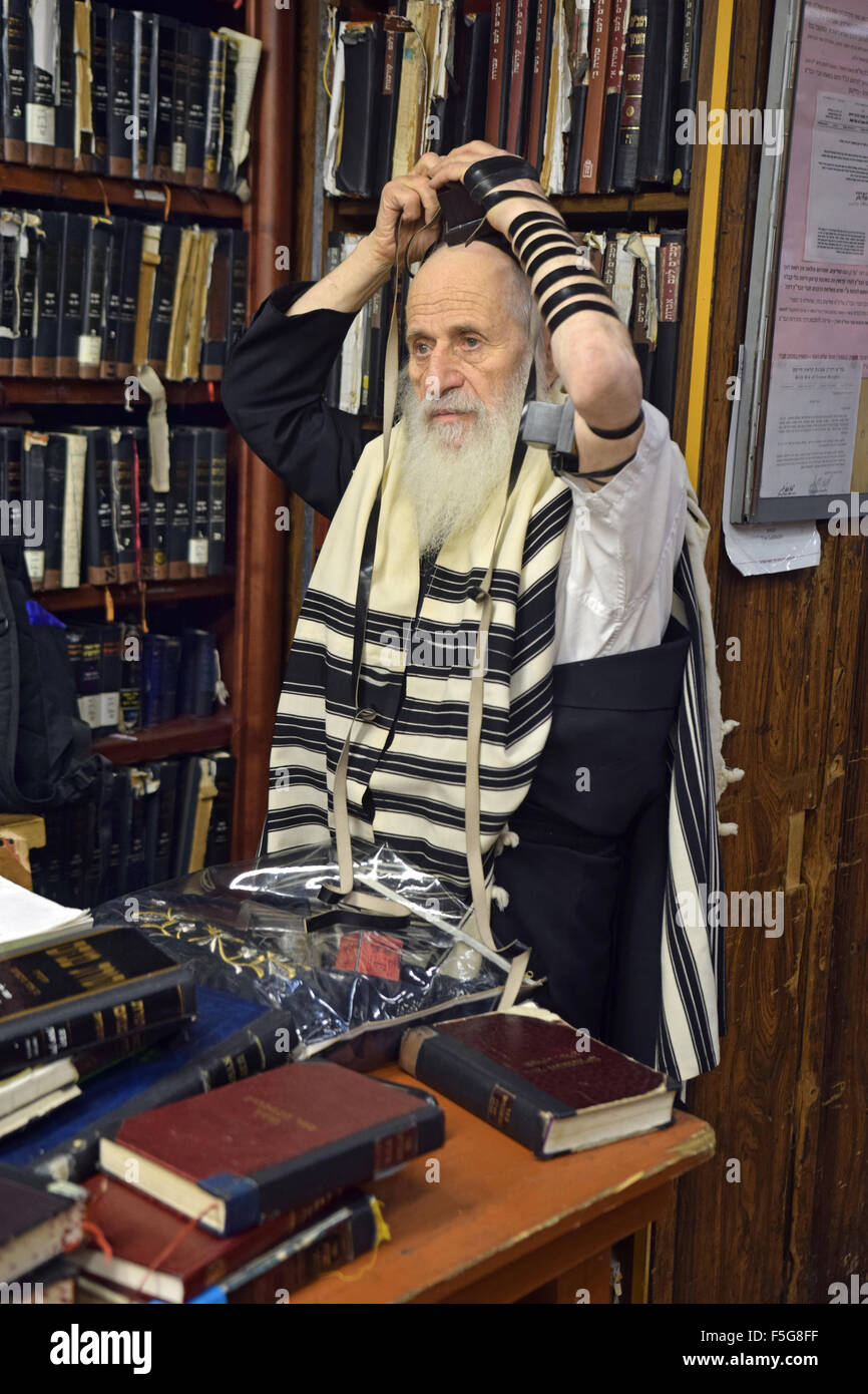 An older religious Jewish man putting on phylacteries teffilin at morning services at a synagogue in Brooklyn, New - Stock Image