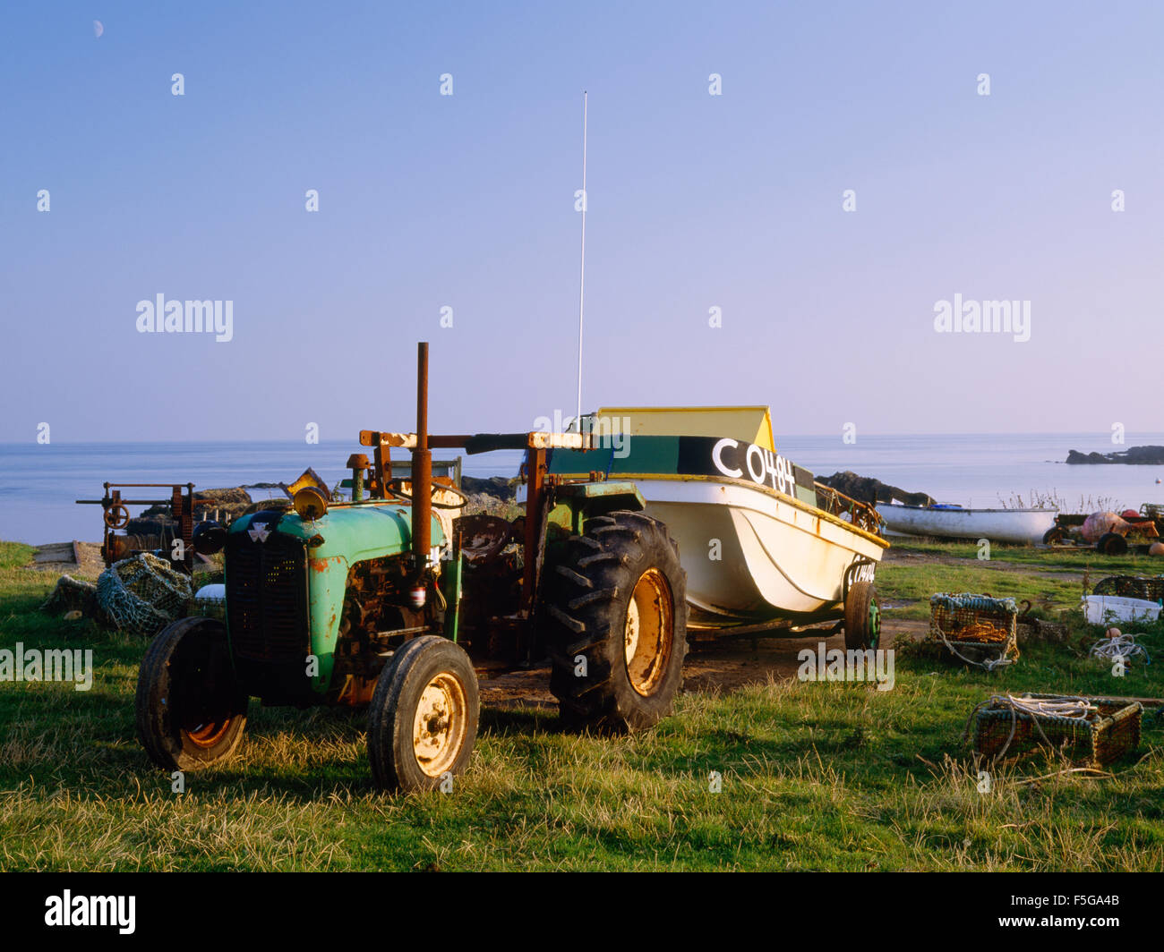 Fishing boat drawn up out of the sea by old tractor and trailer, Cafn, Bardsey Island, North Wales, UK Stock Photo
