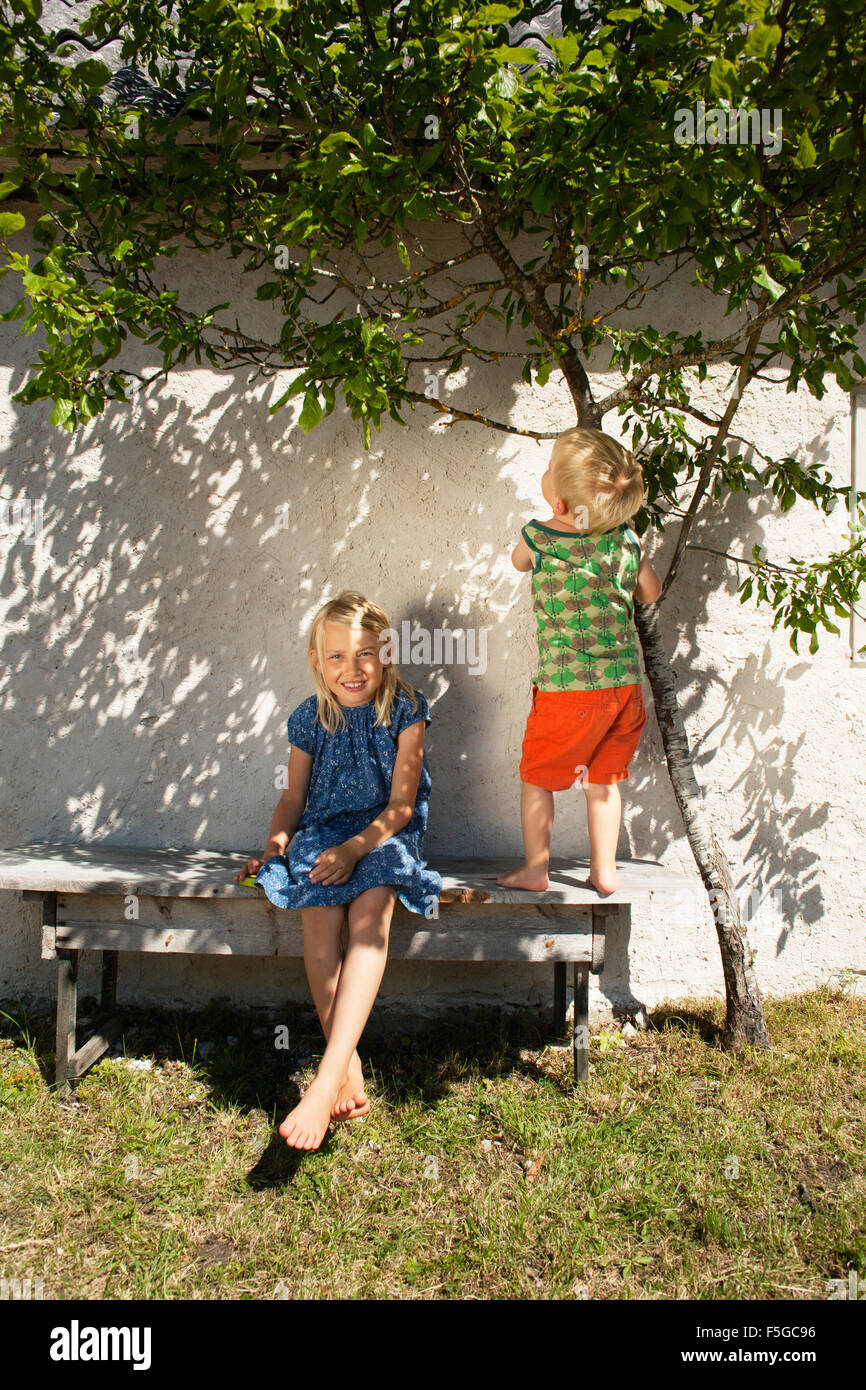 Sweden, Gotland, Faro, Girl (8-9) with brother (2-3) on back yard bench - Stock Image