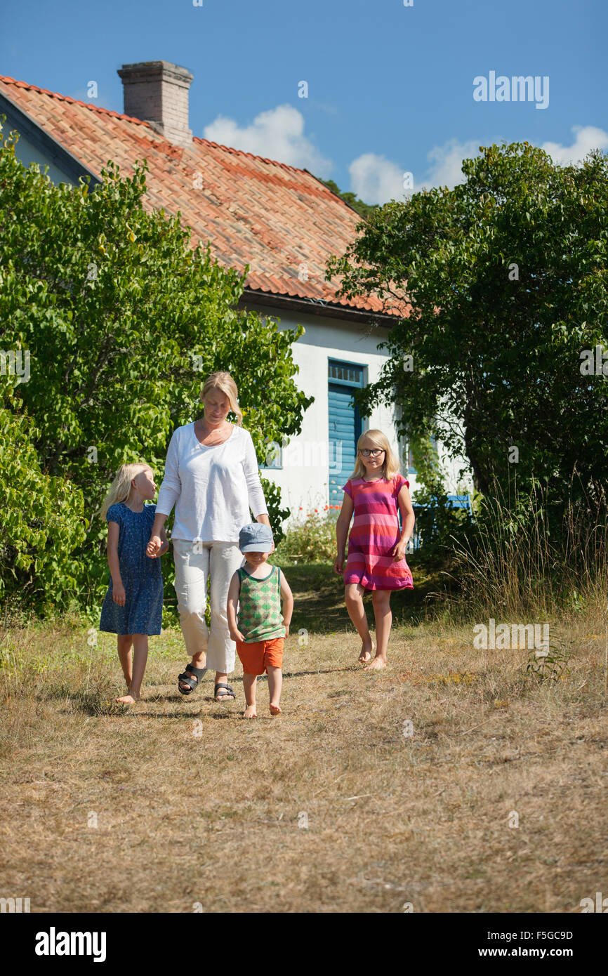 Sweden, Gotland, Faro, Mother with daughters (8-9, 10-11) and son (2-3) in backyard - Stock Image
