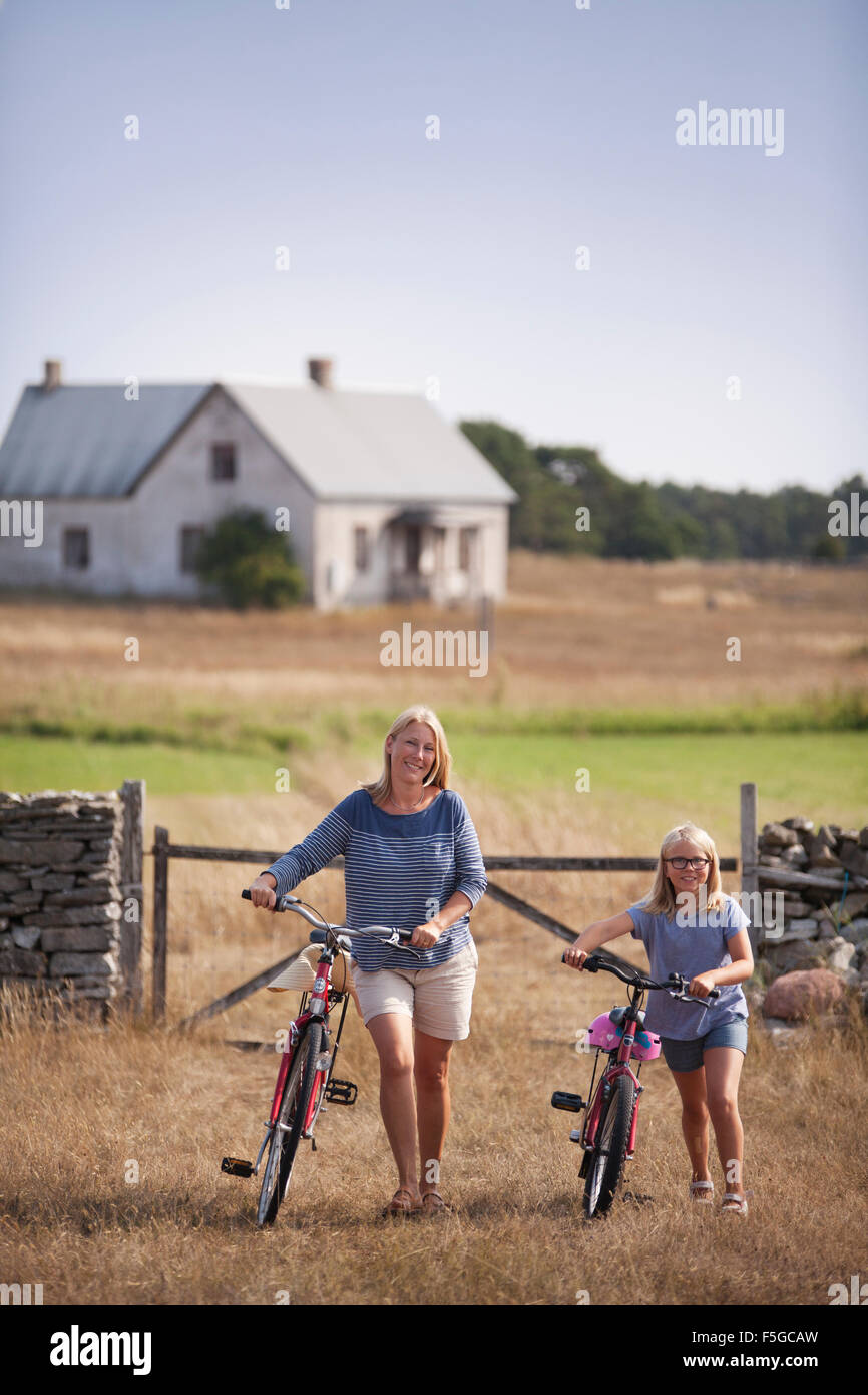 Sweden, Gotland, Faro, Mother and daughter (10-11) wheeling bicycles at farm - Stock Image