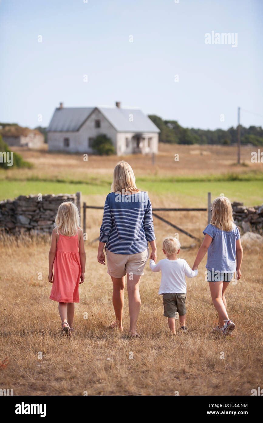 Sweden, Gotland, Faro, Mother with son (2-3) and daughters (8-9, 10-11) walking in farm yard Stock Photo