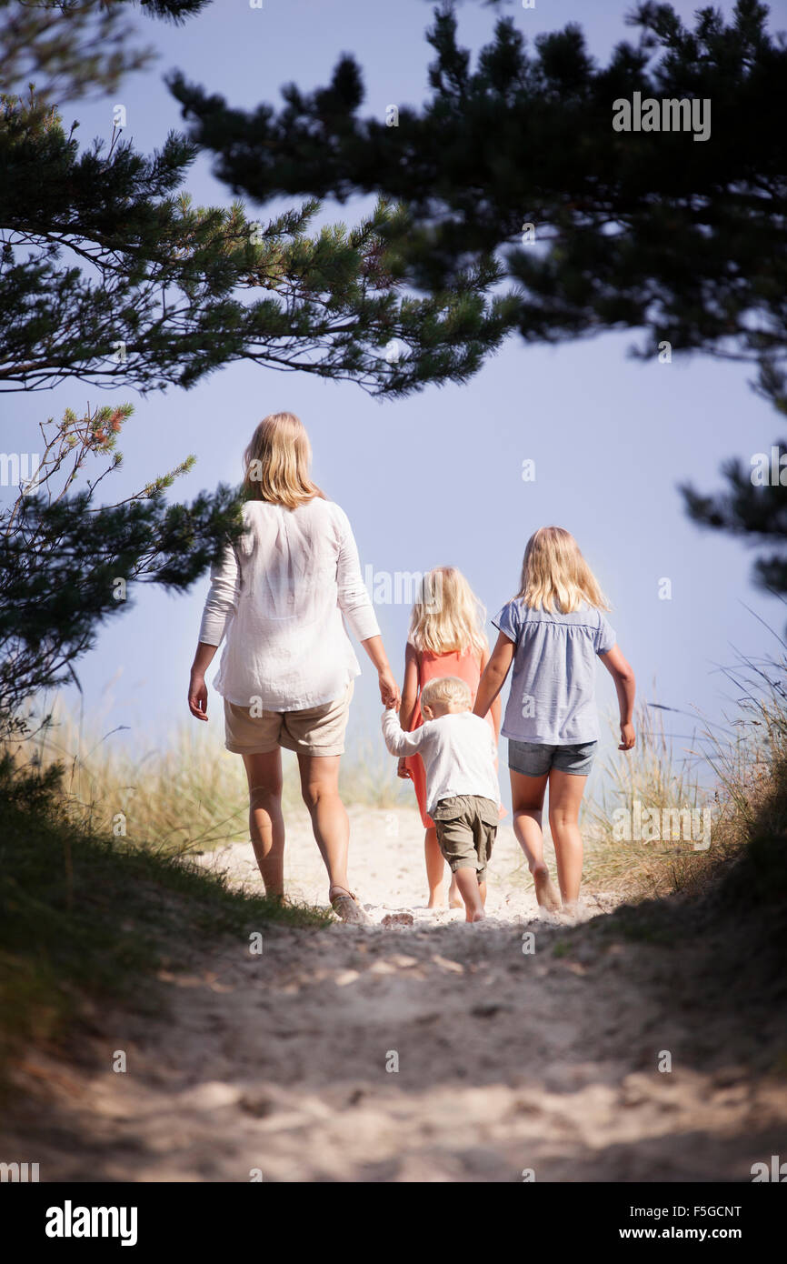Sweden, Gotland, Faro, Skar, Mother with son (2-3) and daughters (8-9, 10-11) walking along footpath - Stock Image