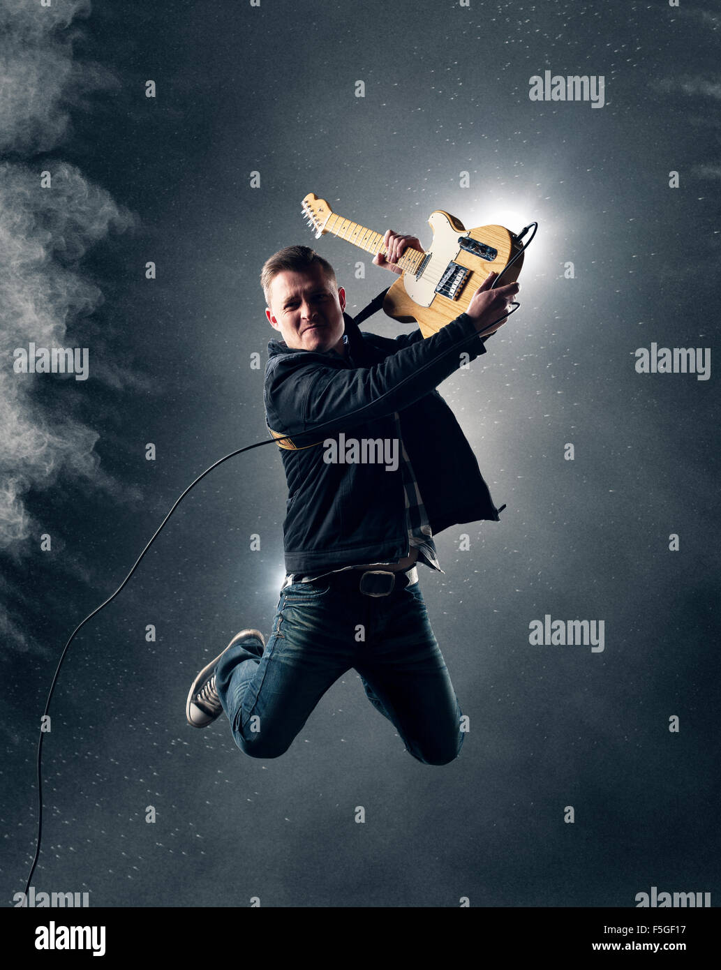 Rock and Roll Guitarist jumping with electric guitar with smoke and powder in background - Stock Image