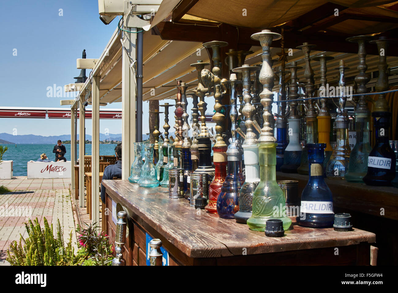 Turkish smoking pipes (hookah) lined up on outdoor bar counter. Stock Photo