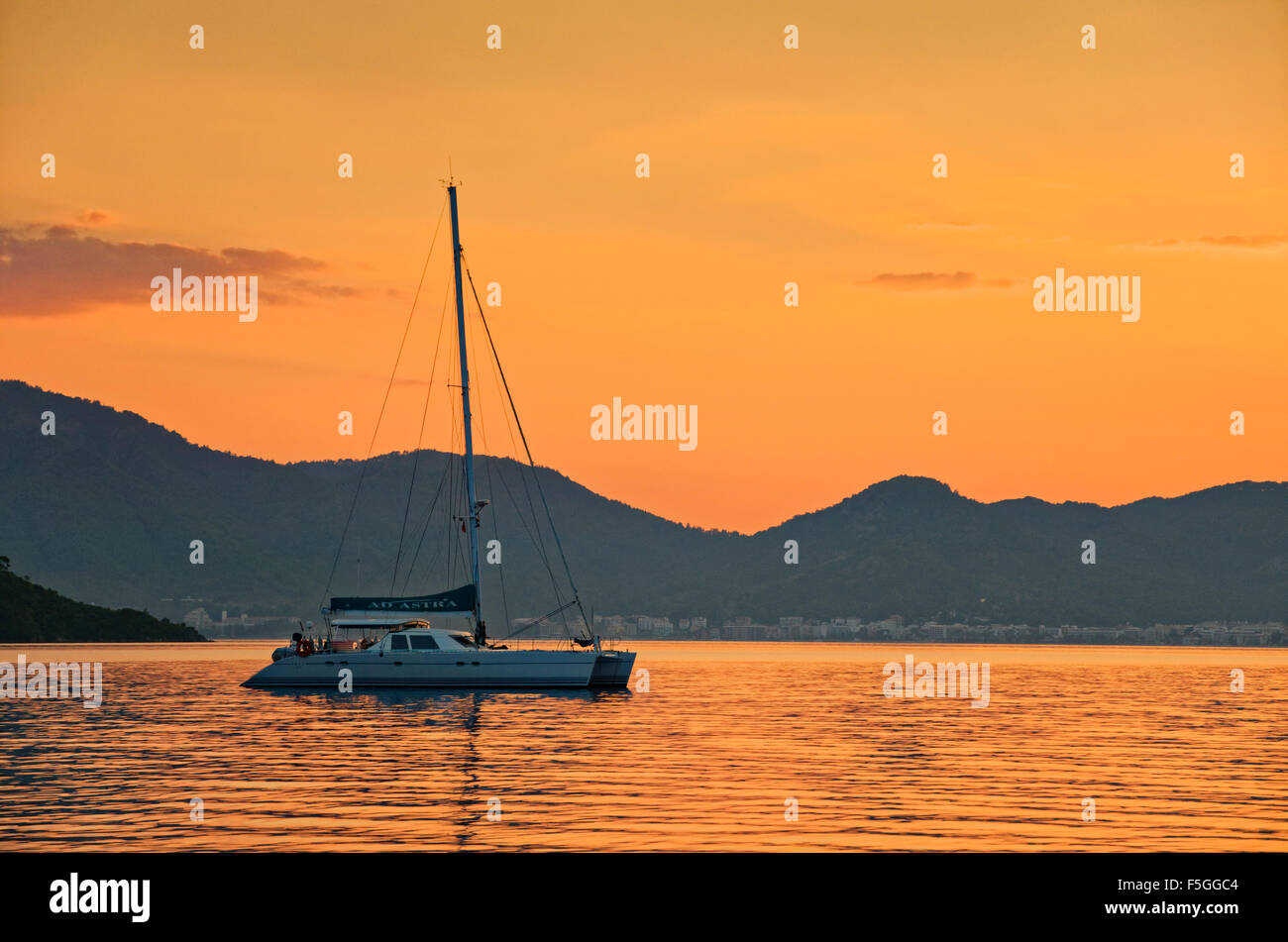 Catamaran anchored off-shore at sunset - Stock Image