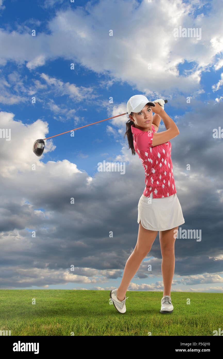 Beautiful young woman playing golf during bright day - Stock Image