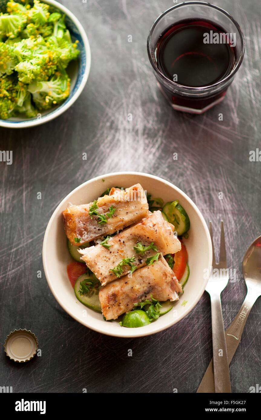 Baked fish served with wine and broccoli Stock Photo