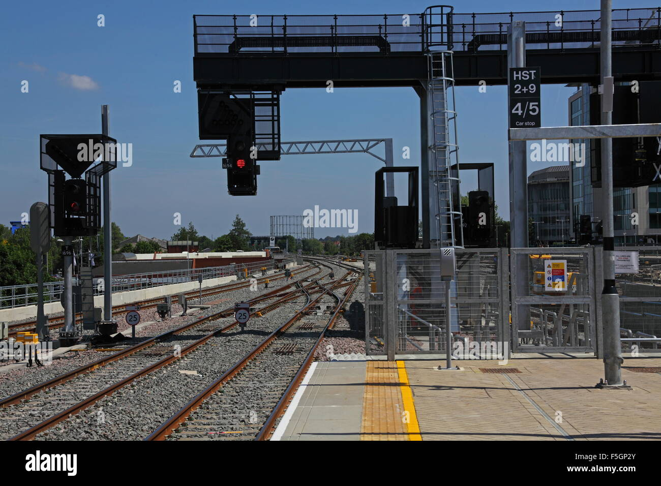 Newly installed overhead signal gantry with a 4 aspect signal for forward movements of trains along the main line - Stock Image