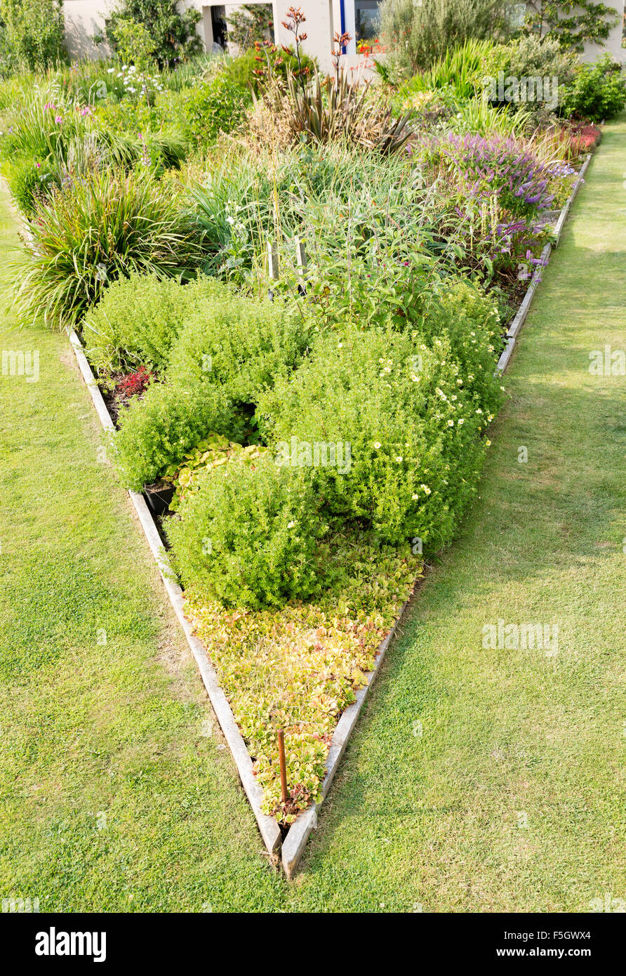 Triangular Raised Flower Bed On Large Garden Lawn Stock