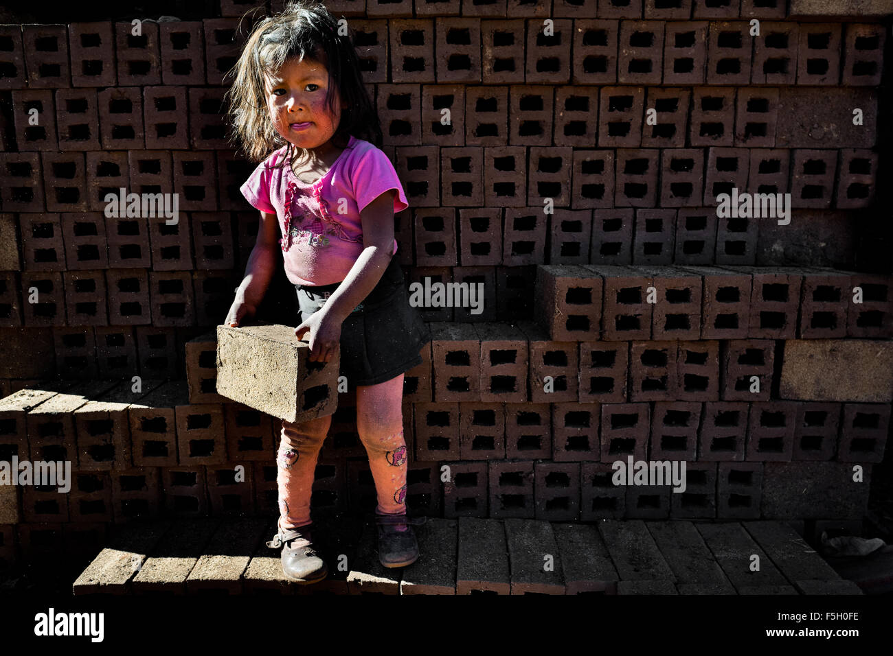 A 5-year-old Peruvian girl carries bricks at a brick factory in the outskirts of Puno, Peru. - Stock Image
