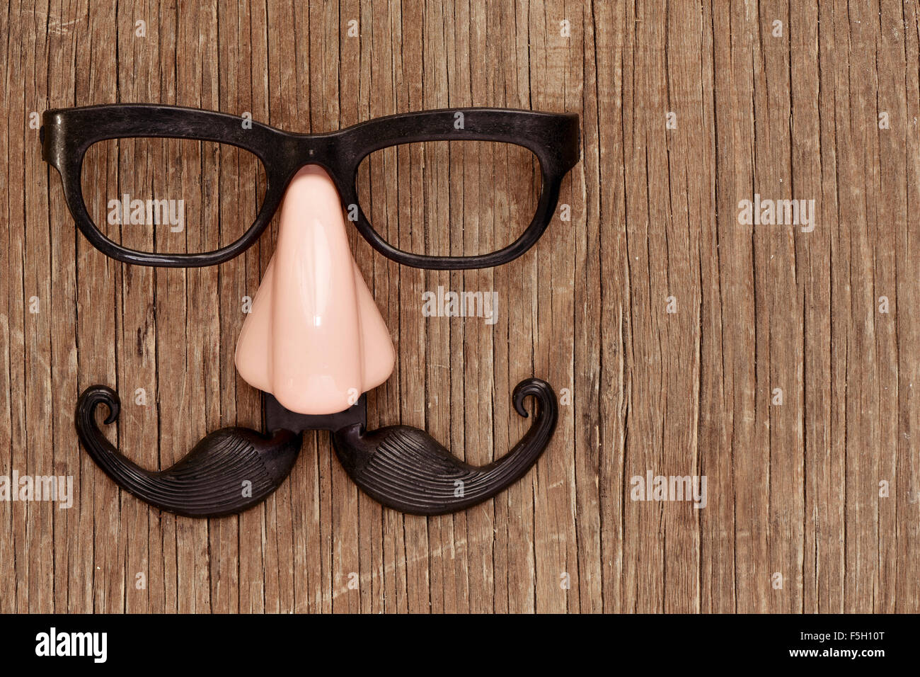 a fake mustache, nose and eyeglasses on a rustic wooden surface - Stock Image