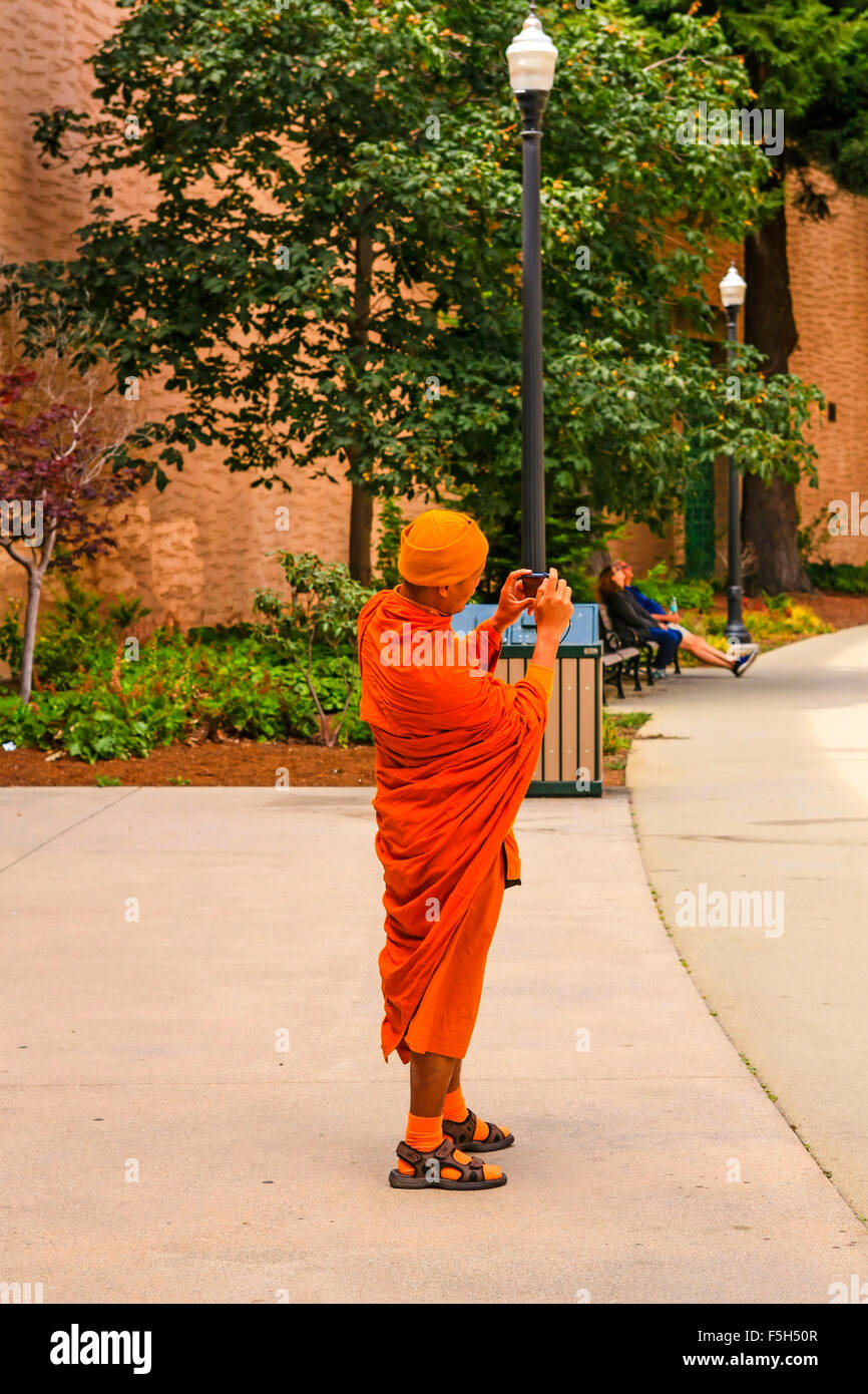 Buddist monk takes tourist photos with a digital camera at the Palace of Fine Arts in the Marina District of San - Stock Image