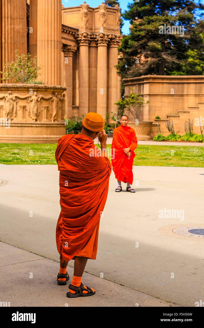 Buddist monks takes tourist photos with a digital camera at the Palace of Fine Arts in the Marina District of San - Stock Image