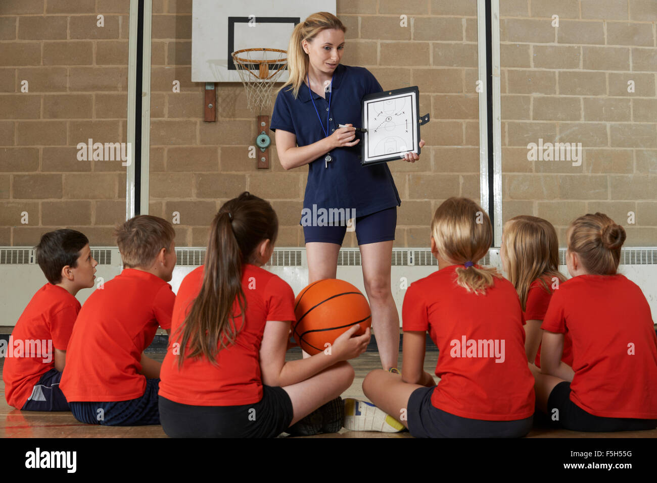 Coach Giving Team Talk To Elementary School Basketball Team - Stock Image
