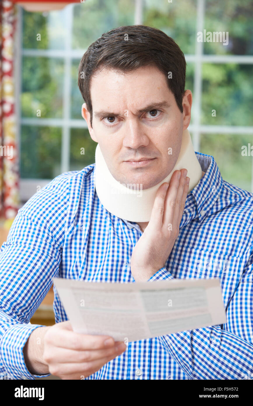 Man Reading Letter After Receiving Neck Injury - Stock Image