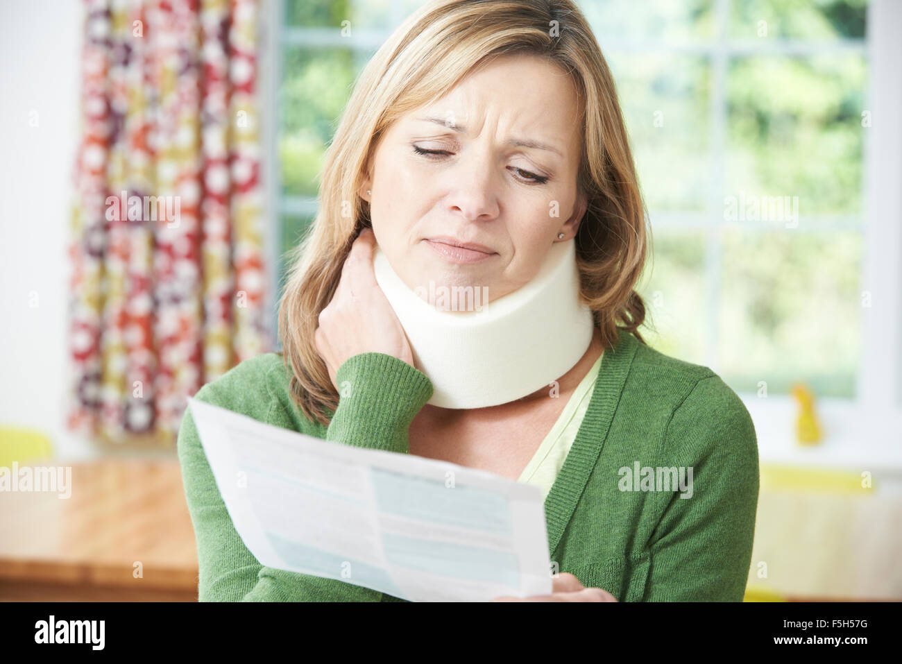 Woman Reading Letter After Receiving Neck Injury - Stock Image