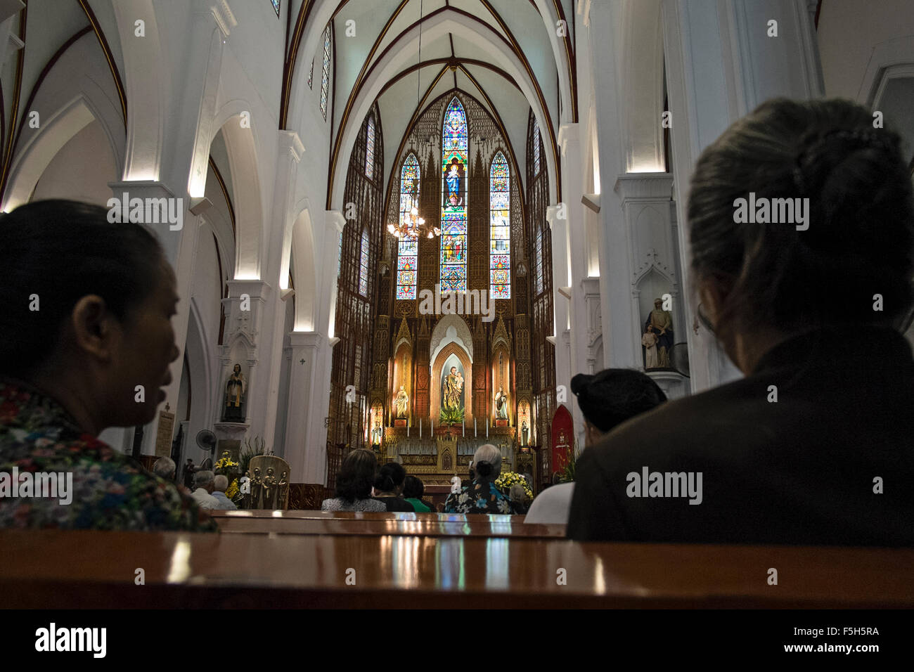 Worshipers in St Josephs Catholic Cathedral, Hanoi, Hoan Kiem, Vietnam - Stock Image