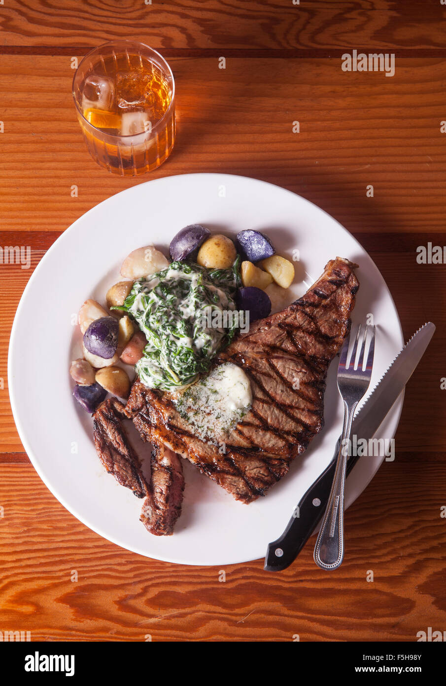 overhead view of steak with potatoes and spinach knife and fork and cocktail on wood table - Stock Image