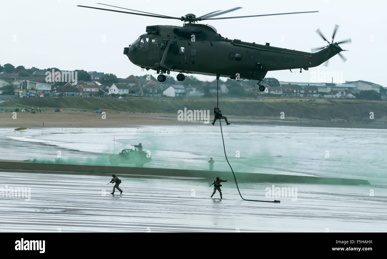 British Royal Marine Commandos fast-line from a helicopter perform a beach assault demonstration for the public, - Stock Image