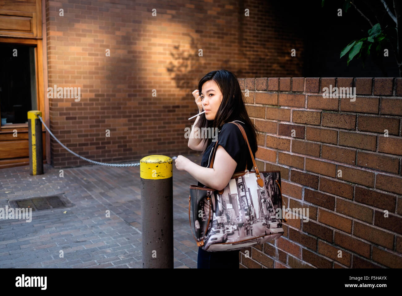 New York City, New York, USA.  August 23, 2015:  A woman stops to adjust her hair with an unlit cigarette in her - Stock Image
