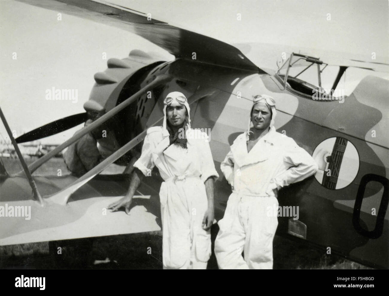 Two airmen in white suit next to a plane with an emblem of the beam, Italy - Stock Image