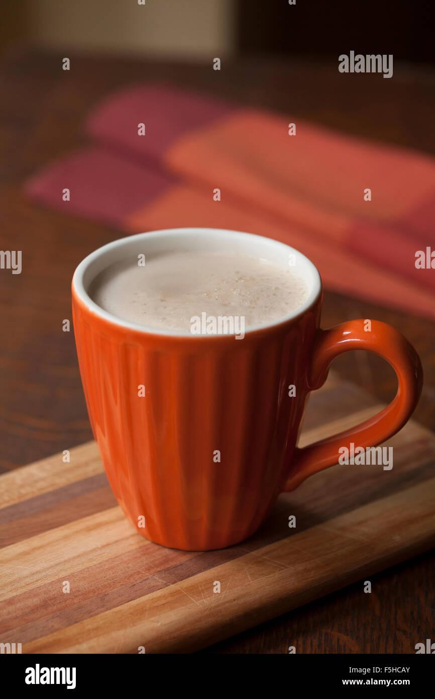 Chai in orange mug with napkin on wood - Stock Image