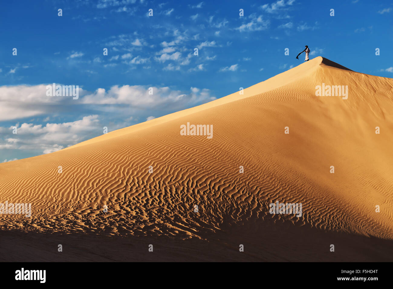 A traditional dressed Moroccan man stands on a sand dune against a cloudy blue sky. - Stock Image